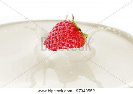 Strawberry Drops Into Milk And Splash