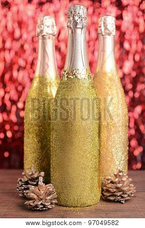 Bottles of champagne with Christmas decoration on bright background