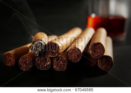 Group of cigars and burning one with whiskey on table, closeup