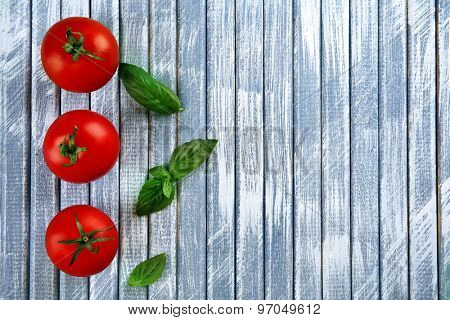 Fresh cherry tomatoes with basil on wooden background