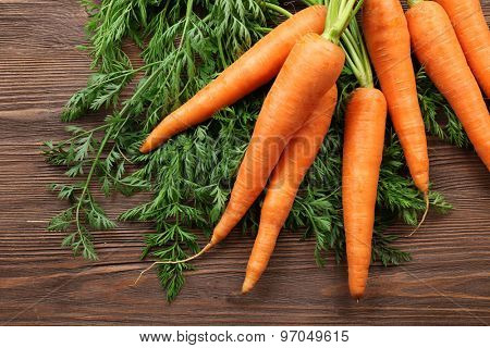 Fresh organic carrots with green tops on wooden table, closeup
