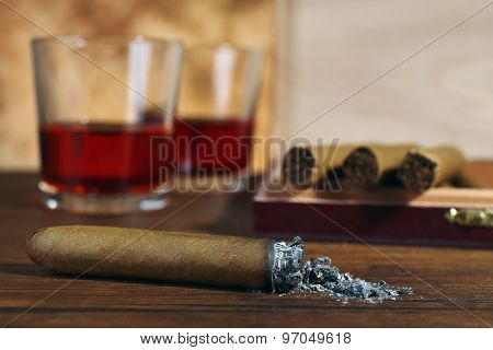 Cigars and burnt one with ash and cognac on wooden table, closeup