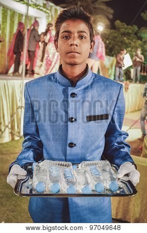 JODHPUR, INDIA - 08 FEBRUARY 2015: Young Indian boy wearing suit holds water bottles on tray working as waiter. Post-processed with grain, texture and colour effect.