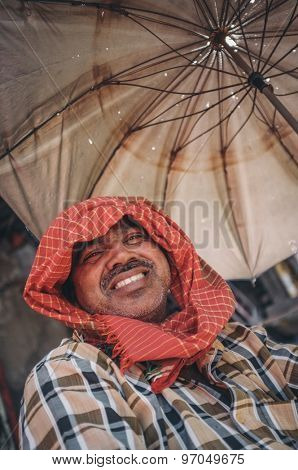 MUMBAI, INDIA - 10 JANUARY 2015: Man sitting under a parasol. Post-processed with grain, texture and colour effect.