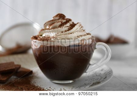 Cup of coffee with cream on color wooden background