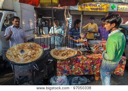 MUMBAI, INDIA - 10 JANUARY 2015: Street vendor makes Halwa poori close to Dhobi Ghat. A sweet bread and type of candy made for breakfast. Customers eat with fingers.