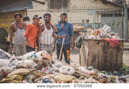 MUMBAI, INDIA - 16 JANUARY 2015: Five adult garbage men pile up garbage on slum street before throwing into garbage truck. Post-processed with grain, texture and colour effect.