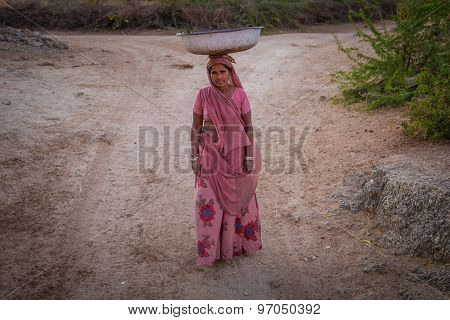 GODWAR REGION, INDIA - 14 FEBRUARY 2015: Indian woman in pink sari stands alone in dirt track with metal container balanced on head.
