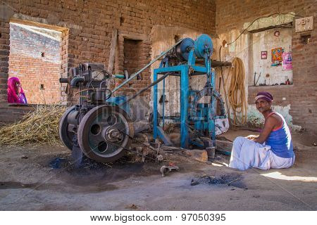 GODWAR REGION, INDIA - 14 FEBRUARY 2015: Mechanic with moustache wearing headscarf and big golden earrings sits inside of workshop next to hammer forging machine.