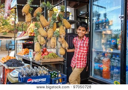 HOSPET, INDIA - 04 FEBRUARY 2015: Indian boy waiting with pineapples in front of store.