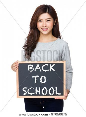 School girl hold with chalkboard and showing phrase of back to school