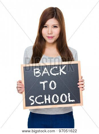 Asian woman hold with blackboard showing phrase of back to school