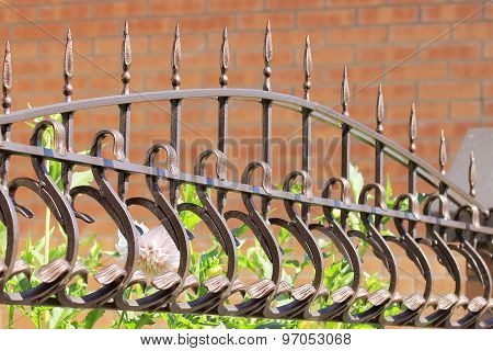 Elegant Metal Wrought Iron Fence Against A Brick Wall