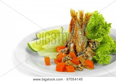 Fried small fish on plate with lettuce and lime isolated on white