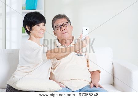 Modern technology, age and people concept. Asian senior couple selfie, using smartphone, self photographing. Family living lifestyle at home.