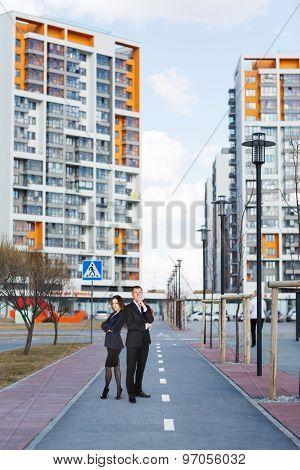 Business people walking along buildings