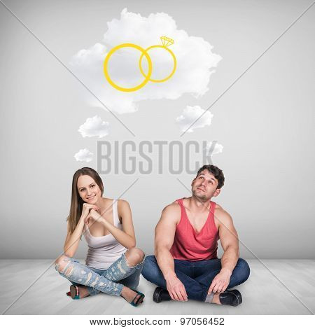 Loving couple sitting on floor in room