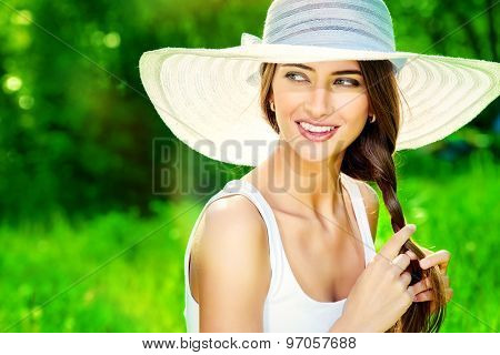 Portrait of a beautiful elegant young woman in light white dress and hat in the summer park. Beauty, fashion. Holidays.