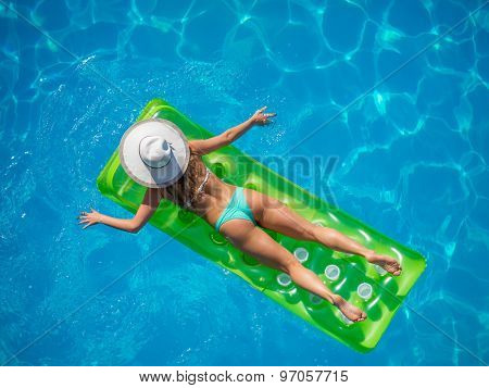 Top view of a  girl in the swimming pool on a lilo