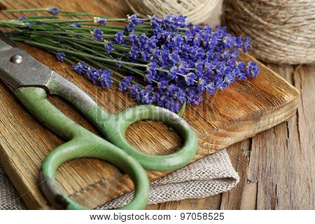 Fresh lavender with rope and scissors on wooden cutting board, closeup