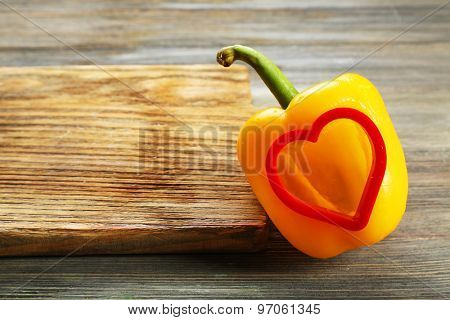 Salad pepper with cut in shape of heart on wooden background
