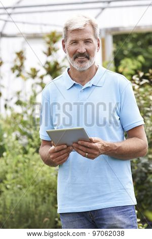 Portrait Of Sales Assistant In Garden Center With Digital Tablet