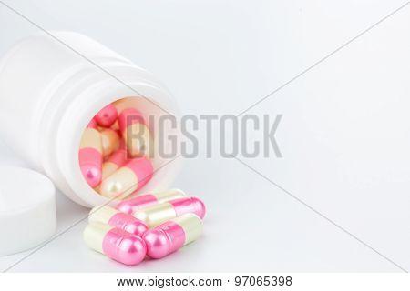 Pink And Yellow Pearl Pills An Pill Bottle On White Background