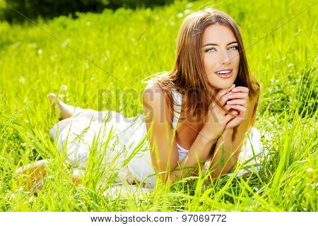 Beautiful happy young woman lying on a grass in the summer park and smiling. Holidays, vacation.