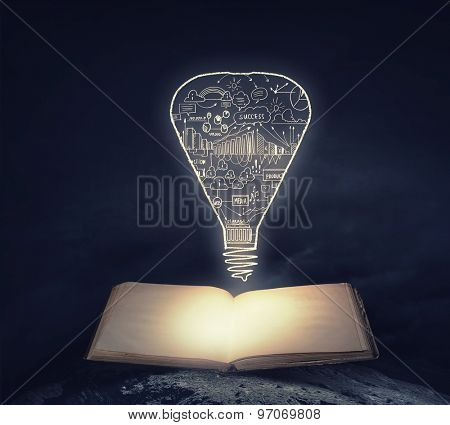Old opened book with business sketches over black background
