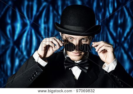 Portrait of an elegant old-fashioned artist man wearing black suit and bowler-hat. Fashion, style. Cinema, theater.