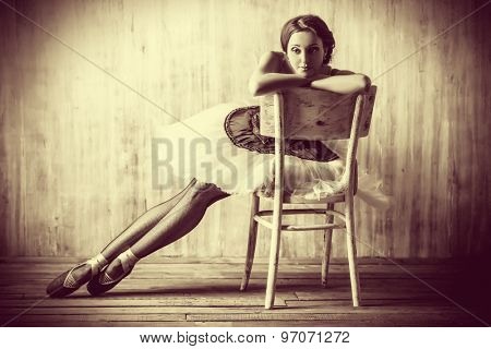 Professional ballet dancer posing at studio over grunge background. Art concept. Toned photo in vintage style.