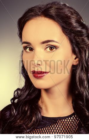 Close-up portrait of young woman with beautiful brunette hair. Make-up, cosmetics.