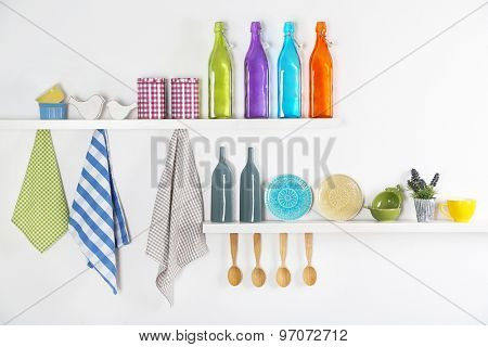 Kitchen utensils on wooden shelves, close up