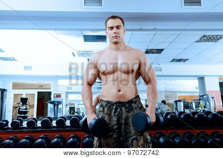 Athletic man working out with dumbbells in a gym.
