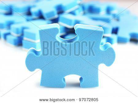 Pile of blue puzzle pieces, closeup