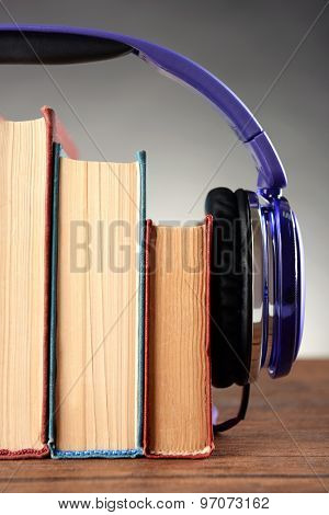 Books and headphones as audio books concept on wooden table on grey background