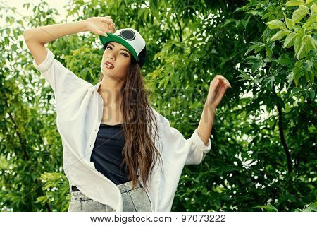 Modern girl wearing casual clothes and a cap posing outdoor. Teenager girl. Youth style. Fashion style.