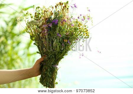 Female hands with bouquet of wildflowers over blue sky background