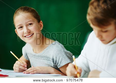 Happy schoolgirl looking at camera while drawing with classmate near by
