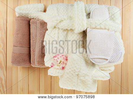 Bathrobe, towels and slippers on wooden table, top view