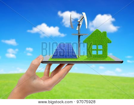 Hand holding tablet with green house, wind turbine and solar panel. Ecology concept.