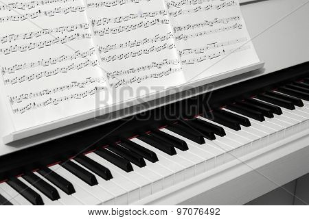 Piano with music notes close up