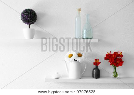 Decorative vases with flowers on wooden shelf  on white wallpaper background