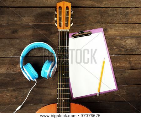 Music recording scene with classical guitar, memo pad and headphones on wooden table, closeup