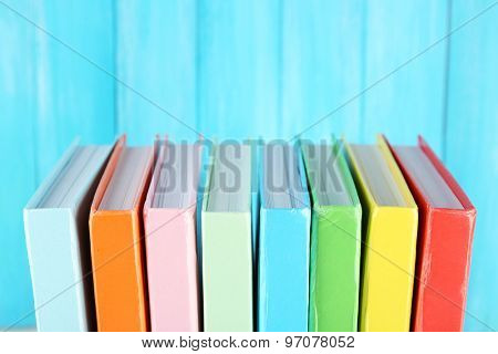 Colorful books on turquoise wooden background