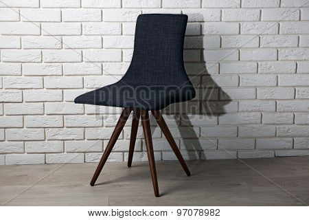 Modern chair on brick wall background