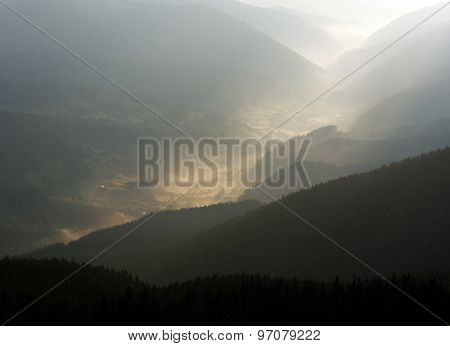 Mountain Valley Village In The Fog And Sun Rays Of Dawn