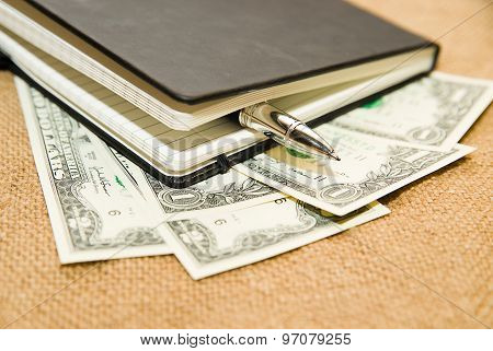 Notebook, Pen And Money On The Old Tissue