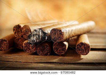 Group of cigars and burning one on wooden table on brown background