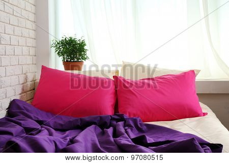 Comfortable bed with pink pillows and purple blanket in bedroom